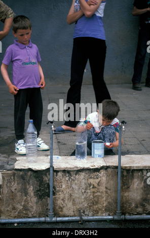 Child collecting water at refugee camp in Tirana, Albania for Kosovar refugees fleeing war in Kosovo, 1999 - Stock Photo
