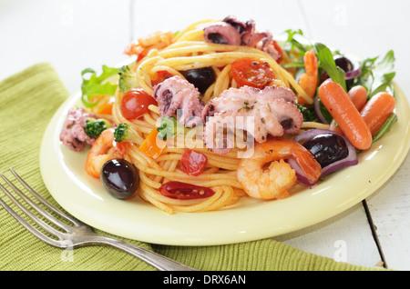 Seafood spaghetti marinara pasta dish with octopus, shrimps, cherry tomatoes and olives - Stock Photo