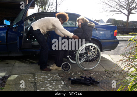 united kingdom west sussex an elderly woman being helped by carer to get into a car - Stock Photo
