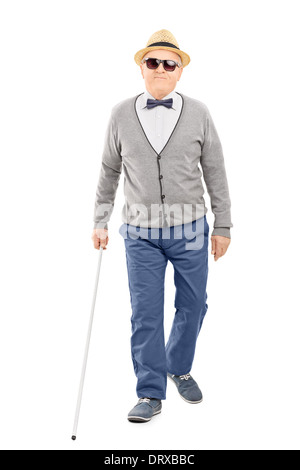 Full length portrait of blind senior gentleman walking with a stick - Stock Photo