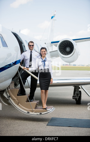 Confident Airhostess And Pilot Standing On Private Jet's Ladder - Stock Photo