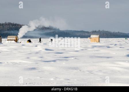 Ice fishermen fishing on a frozen lake near their hut. - Stock Photo