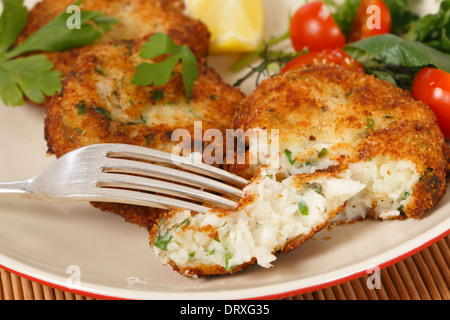 Easy to make fishcakes, with steamed fish crumbled into mashed potato and parsley mix,  served with a salad - Stock Photo