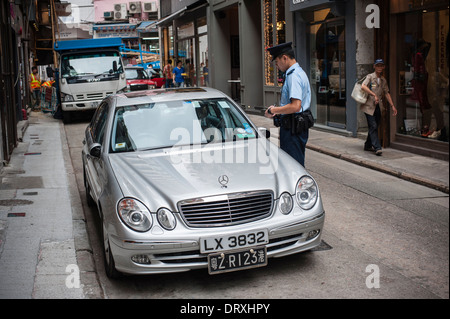Police man fining a wrongly parked mercedes car in Gough Street. The car has also a mainland China number plate - Stock Photo