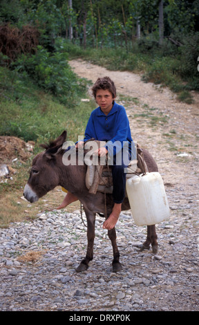 Boys riding donkey in rural Albania - Stock Photo