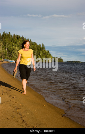 A woman walks barefoot on the sandy beach. - Stock Photo