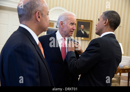 US President Barack Obama adjusts Vice President Joe Biden's American flag pin as they wait in the Oval Office with - Stock Photo