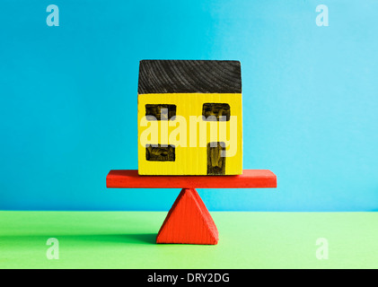 Toy house on weighing scales - Stock Photo