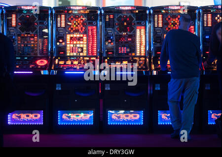 London, UK - 4 February 2014: a man plays at slot machines at the ICE Totally Gaming 2014 show, the biggest event - Stock Photo