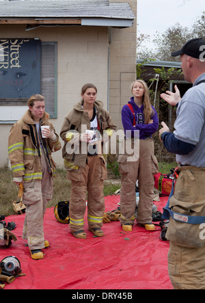 Female students from high school fire training class listen to instructor before training exercise in abandoned - Stock Photo