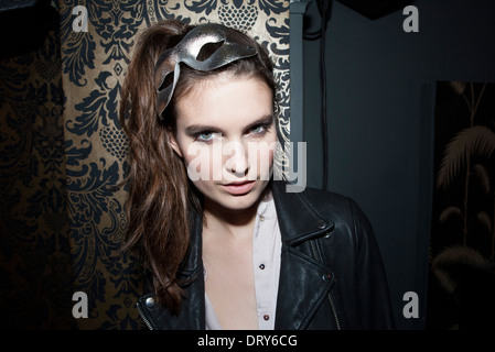 Woman wearing party mask on head, portrait - Stock Photo