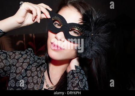 Woman wearing party mask, portrait - Stock Photo