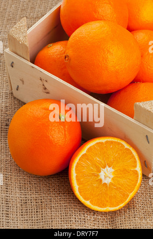 Whole and cut organic oranges in wooden crate on burlap - Stock Photo
