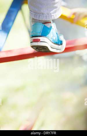 Child climbing on jungle gym, low section - Stock Photo