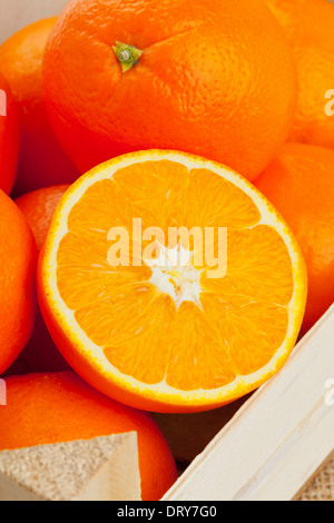 Whole and cut organic oranges in wooden crate - Stock Photo