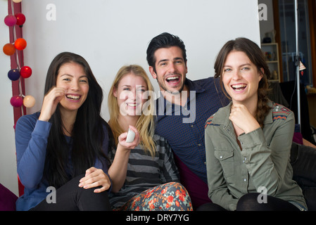 Friends watching movie at home together - Stock Photo