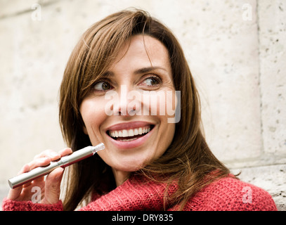 Woman smoking electronic cigarette, smiling - Stock Photo