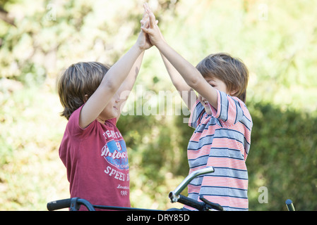 Boys on bicycles giving high fives - Stock Photo