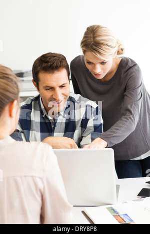 Colleagues gathered around laptop collaborating on work project - Stock Photo