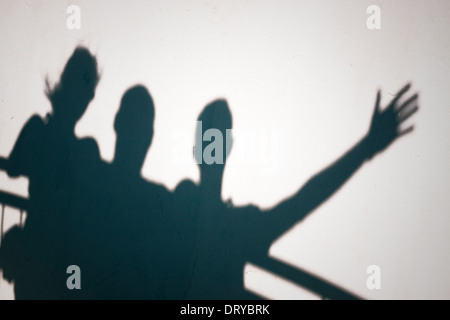 Creative photo of three people shadows on white wall gesturing - Stock Photo