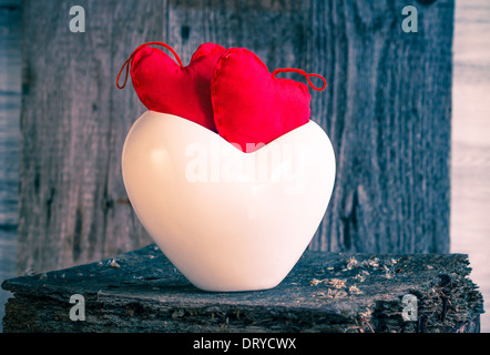 Two hearts in a white cup on a wooden board - Stock Photo