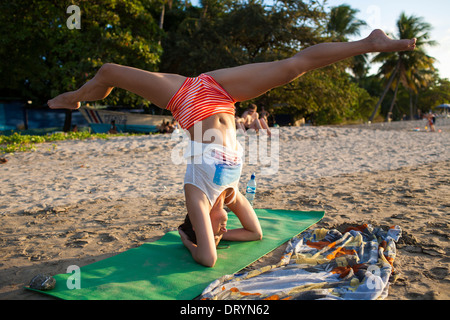 A woman performs a yoga pose or movement balancing on her head on the beach at Playa Tamarindo in Guanacaste, Costa - Stock Photo