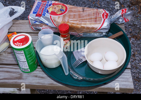 Cooking supplies setup for making French Toast in cast iron Dutch Oven pots - Stock Photo