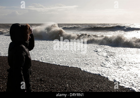 Lady on beach watching high tide storm waves - Stock Photo
