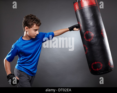 Boy hitting the punching bag on gray background - Stock Photo