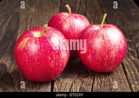 Three red apples on wooden table - Stock Photo