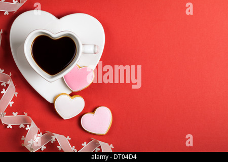 lack coffee with cookies in shape of heart on red paper background. Composition for Valentines Day. Top view. Copy - Stock Photo