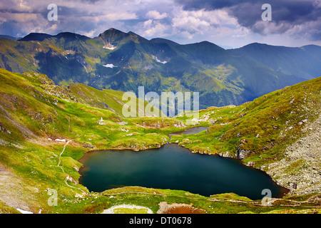 Panoramic view of Lake Capra from Fagaras mountains - Stock Photo