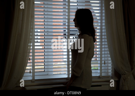 Silhouette of woman standing by a window. Over shoulder back/side view. - Stock Photo