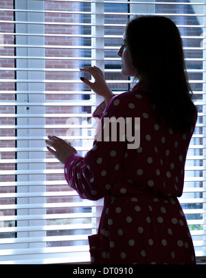 Silhouette of woman wearing a dressing gown looking out of a window. Over shoulder back/side view. - Stock Photo