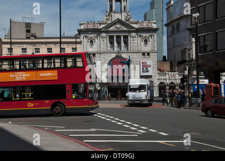 London red double decker bus passing in front of the Victoria Palace Theatre, Victoria Street. - Stock Photo