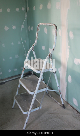 Step stool and wall daubed with plaster - Stock Photo