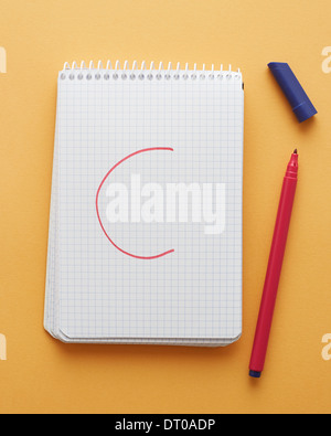 C letter handwritten in notebook page on yellow background alphabet - Stock Photo