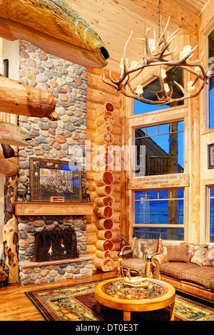 The great room in a modern log cabin, with rustic decor, and furniture.