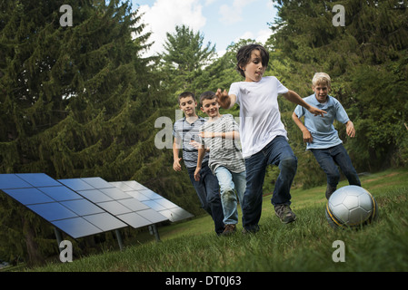 Woodstock New York USA group of boys running after ball past solar panels - Stock Photo