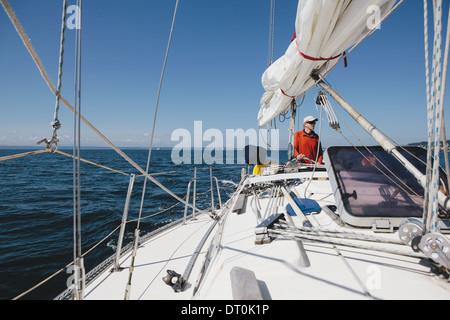 Washington State USA Middle aged man steering sailboat on Puget Sound - Stock Photo