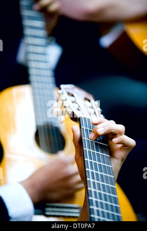Close up of hands playing guitars - Stock Photo
