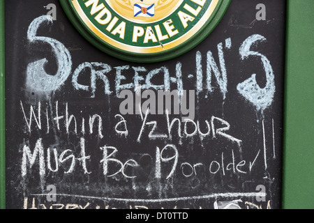 Sign outside a bar in George Street St Johns Newfoundland offering Screech-Ins an initiation ceremony. The person - Stock Photo
