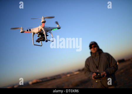 Young man flying Phantom Drone outdoors at sunset - Stock Photo