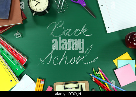 Back to School Supplies on Green Chalkboard Background - Stock Photo