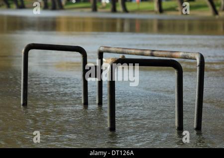 bike racks & rising floodwater near River Great Ouse, Bedford, UK - Stock Photo