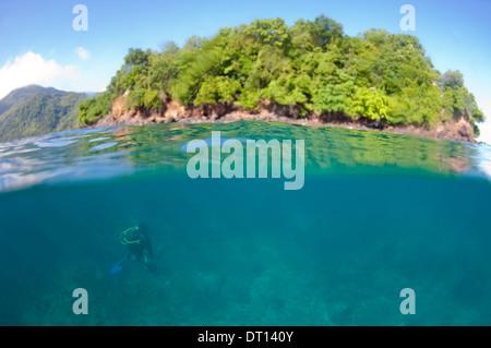 Half and half shot with island and scuba diver, Opposite Tenate Headland, Halmahera, Maluku Islands, Indonesia - Stock Photo