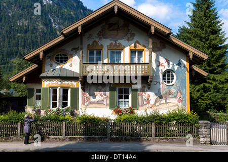 Tourist photographs painted facade of Grimms Fairy Tale Little Red Riding Hood in Oberammergau in Bavaria, Germany - Stock Photo