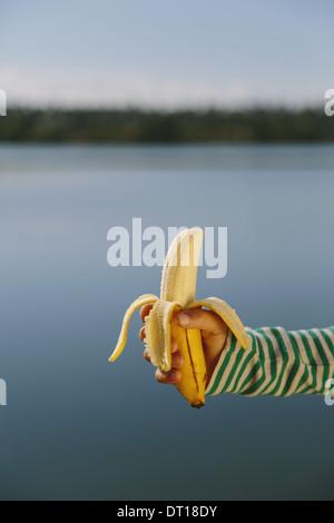Seattle Washington USA Nine year old girl holding organic peeled banana - Stock Photo