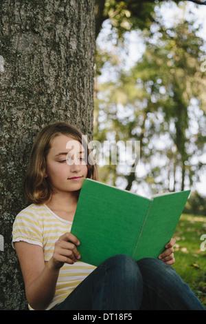 Seattle Washington USA Nine year old girl sitting under tree reading book - Stock Photo
