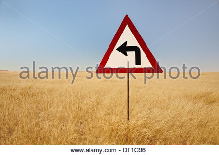 Namibia turn left traffic sign middle tall grasses Namibia - Stock Photo